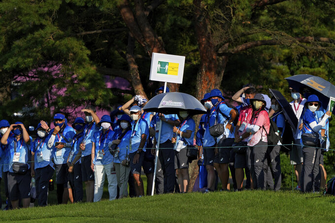 """Volunteers wearing face masks to help curb the spread of the coronavirus hold a social distancing sign as they gather in-line to watch the final round of the men's golf event at the 2020 Summer Olympics on Sunday, Aug. 1, 2021, in Kawagoe, Japan. Japan is playing host to the Tokyo Olympics. But the capital, as well as other populous areas, are in the middle of a government-declared """"state of emergency"""" to curb surging COVID-19 infections. (AP Photo/Andy Wong)"""