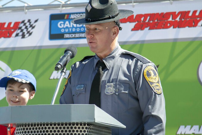 Virginia State Police Trooper B.S. Draper talks to race fans about having a designated driver before the NASCAR Gander Outdoors Truck Series race at Martinsville Speedway in Martinsville, Va. Saturday, March 23. (AP Photo/Matt Bell) (AP Photo/Matt Bell)