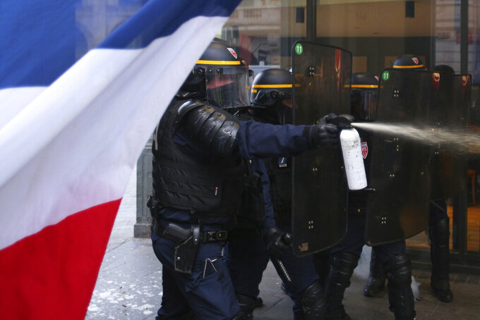 """FILE - In this Jan.11 2020 file photo, a police officer uses gas during a demonstration in Lille, northern France. A summer of incidents, from insults to attacks, some deadly, has built into a crescendo of violence. But has France really grown more """"savage"""" as Interior Minister Gerald Darmanin says? Or is the problem a growing sense of insecurity fueled by the word """"savage"""" itself, as Justice Minister Eric Dupond-Moretti contends? The verbal jousting is causing divisions, and worrying critics who say the interior minister is exploiting the language of the far right to help President Emmanuel Macron's party win upcoming elections. (AP Photo/Michel Spingler, File)"""