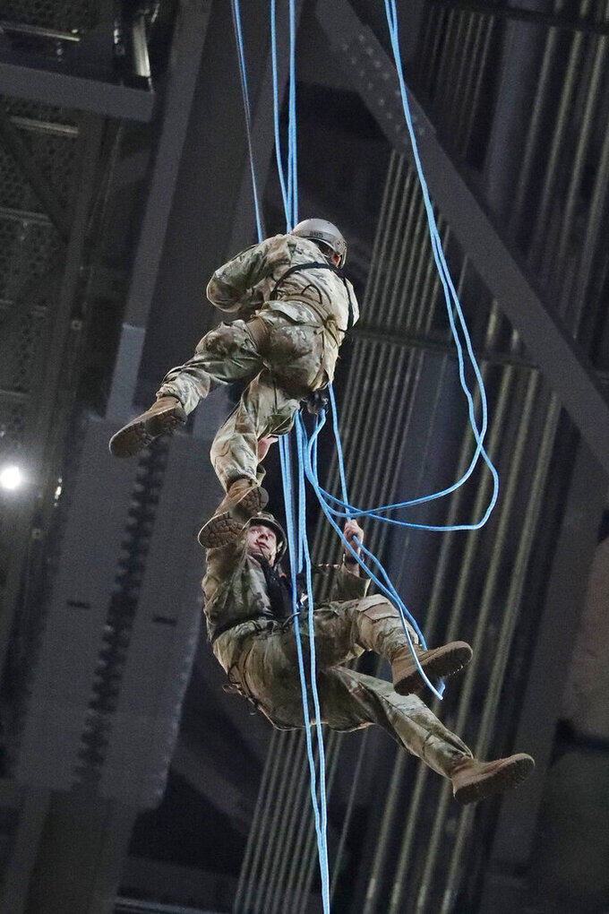 U.S. Army soldiers rappelling into the Mercedes-Benz Stadium as a Salute to service work on tangled rope lines before an NFL football game between the Atlanta Falcons and the Tampa Bay Buccaneers, Sunday, Nov. 24, 2019, in Atlanta. The soldiers made it safley to the field. (AP Photo/John Bazemore)