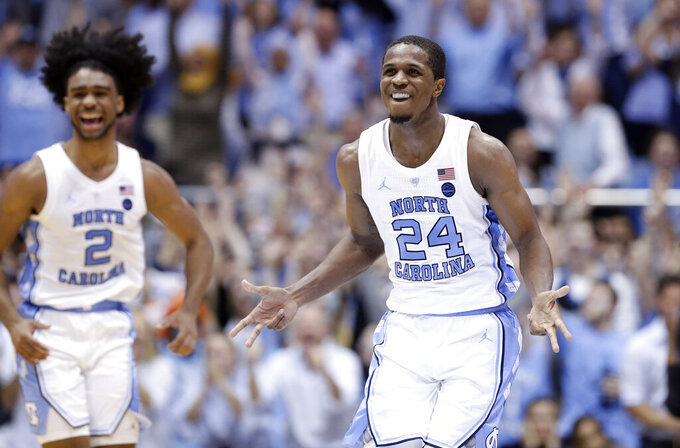 North Carolina's Kenny Williams (24) and Coby White (2) react following a play against Duke during the second half of an NCAA college basketball game in Chapel Hill, N.C., Saturday, March 9, 2019. North Carolina won 79-70. (AP Photo/Gerry Broome)