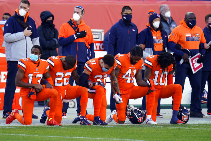 Members of the Denver Broncos take a knee during the national anthem before an NFL football game against the Buffalo Bills, Saturday, Dec. 19, 2020, in Denver. (AP Photo/David Zalubowski)