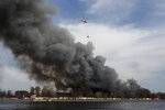 a Russian Emergency Situations Ministry helicopter dumps water on a large-scale fire at the Nevskaya Manufaktura textile factory founded by English merchant J. Thornton in 1841, in St. Petersburg, Russia, Monday, April 12, 2021. The emergencies ministry said the fire had broken out over several floors of the red-brick Nevskaya Manufaktura building on the Oktyabrskaya Embankment of the Neva River. (AP Photo/Dmitri Lovetsky)