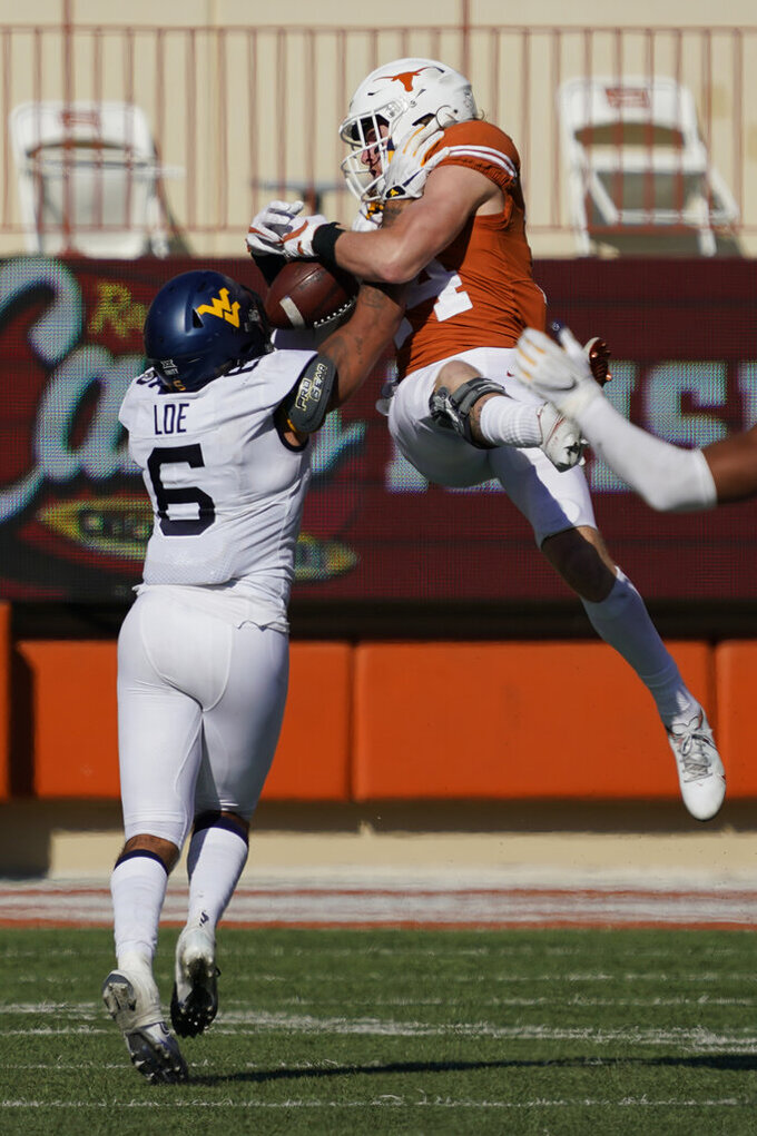 Texas' Brenden Schooler (14) tries to catch a pass as West Virginia's Dreshun Miller (5) defends during the second half of an NCAA college football game in Austin, Texas, Saturday, Nov. 7, 2020. The pass was incomplete. (AP Photo/Chuck Burton)