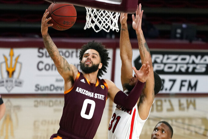 Arizona State guard Holland Woods (0) drives past Arizona guard Terrell Brown Jr. during the first half of an NCAA college basketball game Thursday, Jan. 21, 2021, in Tempe, Ariz. (AP Photo/Rick Scuteri)