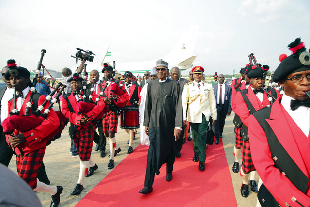 FILE - In this Aug. 19, 2017, file photo released by the Nigeria State House, Nigeria's President Muhammadu Buhari, center, walks upon his arrival at the airport in Abuja, Nigeria, after returning from more than three months in London for medical treatment. The coronavirus pandemic could narrow one gaping inequality in Africa, where some heads of state and other elite jet off to Europe or Asia for health care unavailable in their nations but as global travel restrictions tighten, they might have to take their chances at home. (Sunday Aghaeze/Nigeria State House via AP, File)