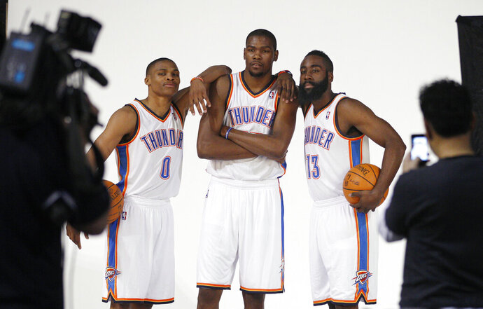 FILE - In this Dec. 13, 2011, file photo, Oklahoma City Thunder's Russell Westbrook (0), Kevin Durant, center, and James Harden (13) pose for a photo for NBA basketball photographers during media day in Oklahoma City. The Thunder are heading into a major transition. Westbrook was the last remaining player from the team that moved from Seattle to Oklahoma City in 2008. Durant, Harden, Serge Ibaka, Paul George and others are all gone. Now Westbrook will soon be on his way to Houston after an 11-year career with the franchise. (AP Photo/Sue Ogrocki, File)