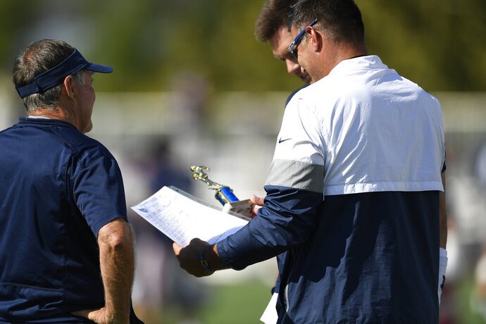 New England Patriots quarterback Tom Brady (12) presents Tennessee Titans head coach Mike Vrabel with a trophy before a combined NFL football training camp Thursday, Aug. 15, 2019, in Nashville, Tenn. (George Walker IV/The Tennessean via AP)