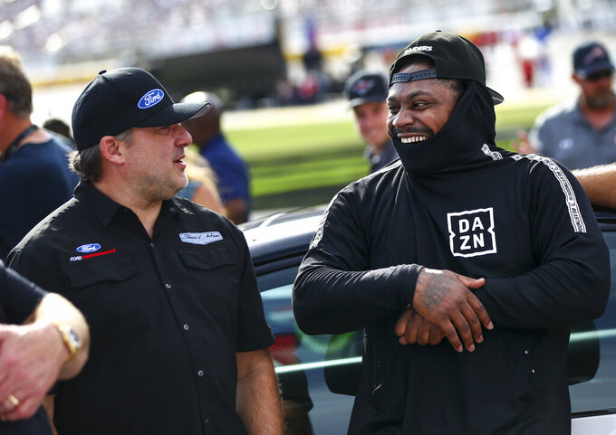 Team owner Tony Stewart, left, talks with former NFL football player Marshawn Lynch before a NASCAR Cup Series auto race at Las Vegas Motor Speedway, Sunday, Sept. 15, 2019. (AP Photo/Chase Stevens)