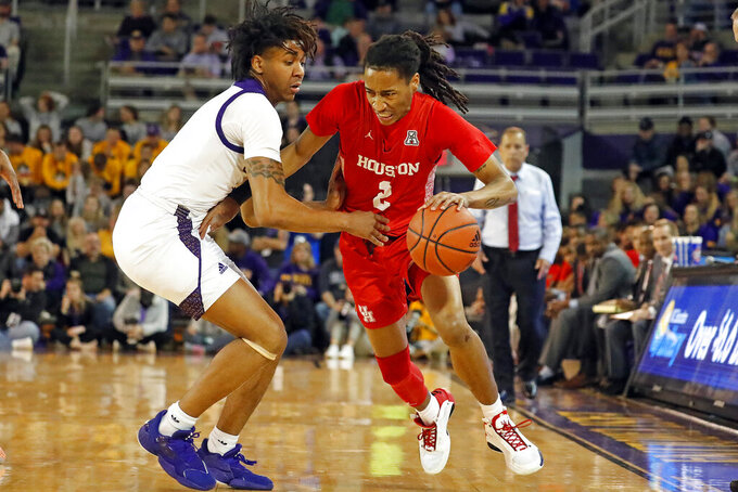 Houston's Caleb Mills (2) drives the ball around East Carolina's Brandon Suggs during the first half of an NCAA college basketball game in Greenville, N.C., Wednesday, Jan. 29, 2020. (AP Photo/Karl B DeBlaker)