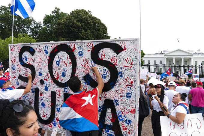 Demonstrators write their solidarity with the Cuban people against the communist government, in a rally outside the White House in Washington, Saturday, July 17, 2021. (AP Photo/Jose Luis Magana)