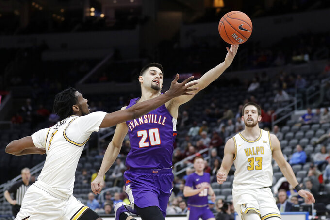 Evansville's Sam Cunliffe (20) reaches for a loose ball as Valparaiso's Javon Freeman-Liberty, left, and John Kiser (33) defend during the first half of an NCAA college basketball game in the first round of the Missouri Valley Conference men's tournament Thursday, March 5, 2020, in St. Louis. (AP Photo/Jeff Roberson)