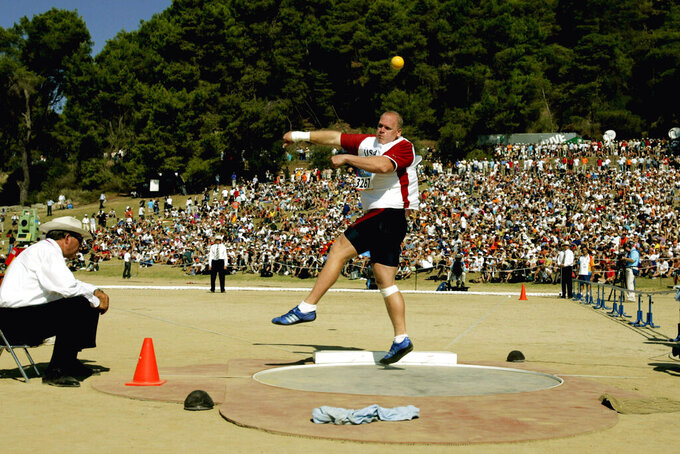 FILE - In this Aug. 18, 2004, file photo, John Godina, of the United States, makes a qualifying throw during the Athens 2004 Olympics men's shot put qualification round in Olympia, Greece. The men's and women's shot put was held in the ancient stadium where the original games were played. (AP Photo/Julie Jacobson, File)