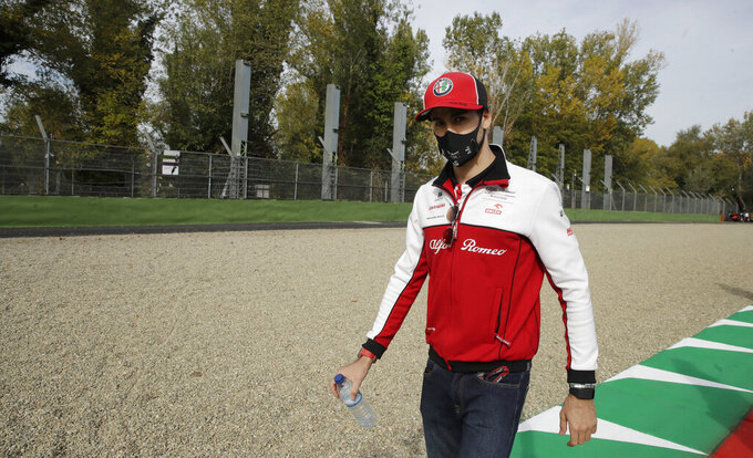 Alfa Romeo driver Antonio Giovinazzi of Italy walks away from the area where Brazilian race car driver Ayrton Senna died, ahead of Sunday's Emilia Romagna Formula One Grand Prix, at the Dino and Enzo Ferrari racetrack, in Imola, Italy, Friday, Oct. 30, 2020. Brazilian Formula One driver Ayrton Senna was killed on May 1, 1994 after his car crashed into a concrete barrier at the Dino and Enzo Ferrari racetrack in Italy. (AP Photo/Luca Bruno)