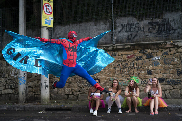 A reveler dressed in Spider-Man costume strikes a pose at the