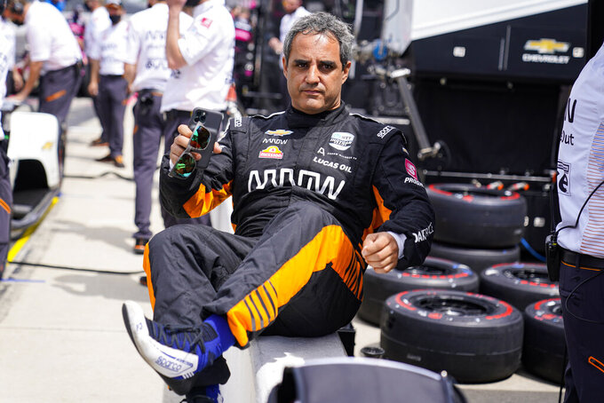 Juan Pablo Montoya, of Colombia, climbs over the pit wall during practice for the Indianapolis 500 auto race at Indianapolis Motor Speedway in Indianapolis, Friday, May 21, 2021. (AP Photo/Michael Conroy)