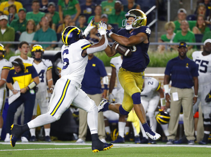 FILE - In this Sept. 1, 2018, file photo, Notre Dame tight end Alize Mack (86) drops a pass as Michigan linebacker Josh Uche (6) defends in the second half of an NCAA football game in South Bend, Ind. No. 4 Michigan might be without defensive star Chase Winovich for Saturday's showdown with No. 10 Ohio State because of an apparent shoulder injury. If he can't play, the Wolverines have so much depth they may be able to overcome it. The Buckeyes, meanwhile, have struggled on defense for much of the year. (AP Photo/Paul Sancya, File)