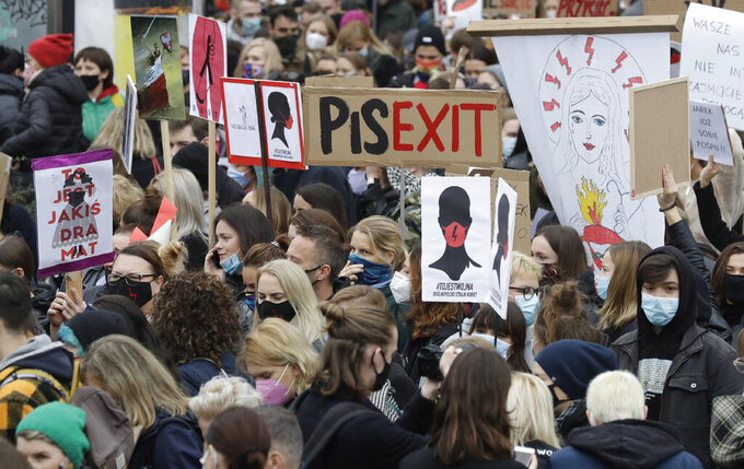 Women's rights activists hold placards during a protest in Warsaw, Poland, Wednesday, Oct. 28, 2020 against recent tightening of Poland's restrictive abortion law. Massive nationwide protests have been held ever since a top court ruled Thursday that abortions due to fetal congenital defects are unconstitutional.(AP Photo/Czarek Sokolowski)