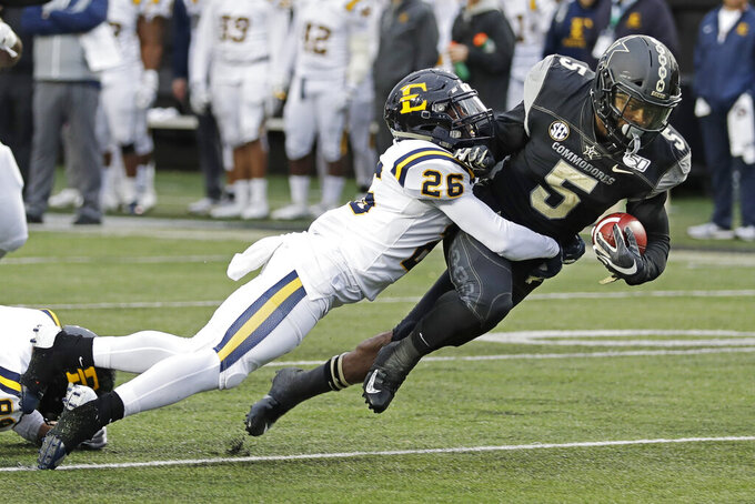 Vanderbilt running back Ke'Shawn Vaughn (5) is stopped by ETSU defensive back Artevius Smith (26) in the first half of an NCAA college football game Saturday, Nov. 23, 2019, in Nashville, Tenn. (AP Photo/Mark Humphrey)