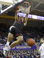 Stanford's Oscar da Silva hangs from the basket after dunking against Washington late in the second half of an NCAA college basketball game Thursday, Feb. 20, 2020, in Seattle. Stanford won 72-64. (AP Photo/Elaine Thompson)