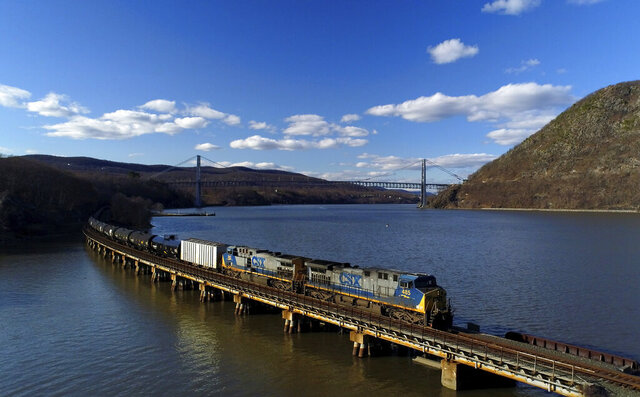 FILE - In this April 26, 2018, file photo a CSX Transportation locomotive pulls a train of tank cars across a bridge on the Hudson River along the edge of Bear Mountain State Park near Fort Montgomery, N.Y. This year's scheduled completion of a $15 billion automatic railroad braking system will bolster the industry's argument for eliminating one of the two crew members in most locomotives. But labor groups argue that single-person crews would make trains more accident prone. (AP Photo/Julie Jacobson, File)