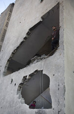 Palestinians check the damage of their home after Israeli airstrikes hit the Hamas' Al-Aqsa TV station building on Monday in Gaza City, Tuesday, Nov. 13, 2018. (AP Photo/Khalil Hamra)