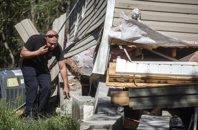 Trey Camardelle surveys the damage to his parents' home from Hurricane Zeta, in Bay St. Louis, Miss., Thursday, Oct. 29, 2020. (Eric Shelton/The Clarion-Ledger via AP)