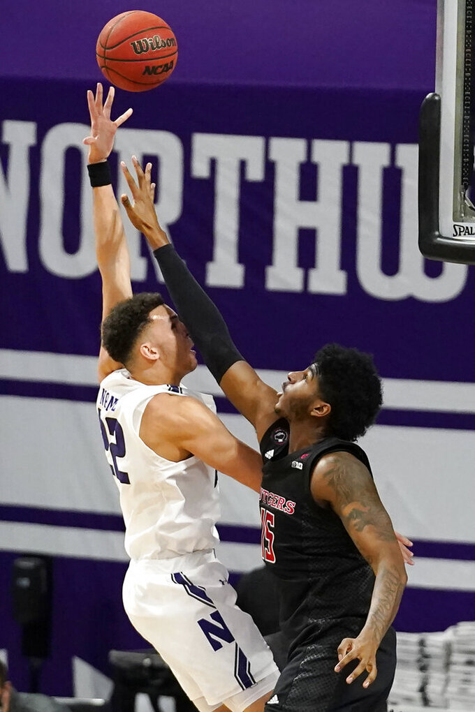 Northwestern forward Pete Nance, left, shoots over Rutgers center Myles Johnson, right, during the first half of an NCAA college basketball game in Evanston, Ill., Sunday, Jan. 31, 2021. (AP Photo/Nam Y. Huh)