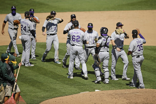 Colorado Rockies celebrate after the 5-1 defeat of the Oakland Athletics at the end of a baseball game Wednesday, July 29, 2020, in Oakland, Calif. (AP Photo/Ben Margot)