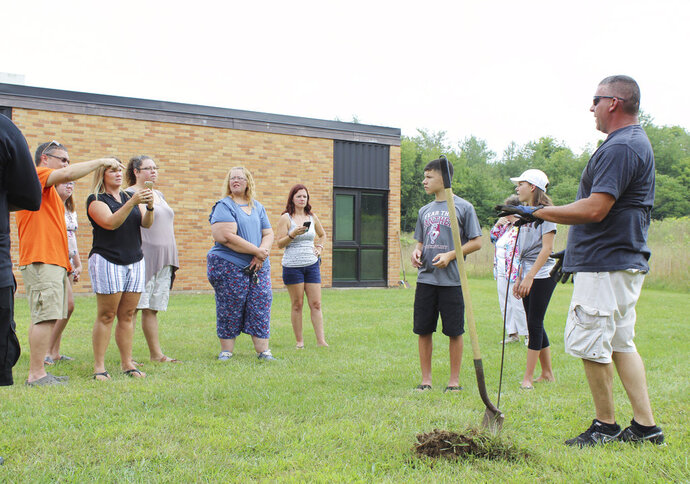 In this Sunday, Aug. 26, 2018, photo classmates that were in the AWARE classes at Coloma Junior High School in 1988 try to find a time capsule that they buried behind the school in Coloma, Mich., that year. The Herald-Palladium reports that the seven classmates and two teachers spent two hours on Sunday digging outside Coloma Junior High in southwestern Michigan. (Alexandra Newman/The Herald-Palladium via AP)