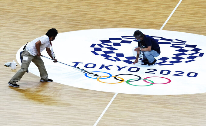 FILE - In this July 23, 2021, file photo, workers clean the handball court at the Yoyogi National Stadium at the 2020 Summer Olympics in Tokyo, Japan. (AP Photo/Pavel Golovkin, File)