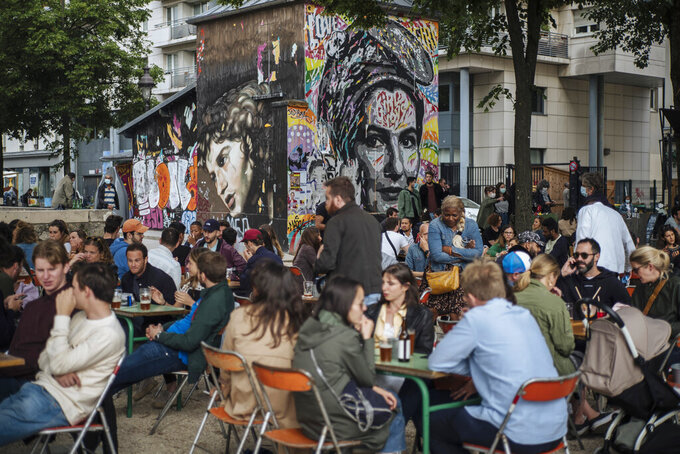 People socialize and drink at a cafe terrace in Paris, France, Saturday, June 5, 2021. (AP Photo/Lewis Joly)