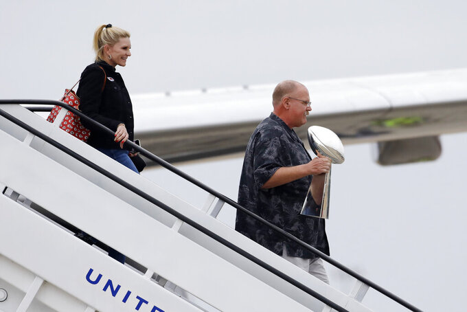 Tammy Reid, left, and her husband, Kansas City Chiefs head coach Andy Reid, right, holding the Vince Lombardi Trophy, exits a plane as his team returns home a day after winning the NFL Super Bowl 54 football game Monday, Feb. 3, 2020, in Kansas City, Mo. The Chiefs defeated the San Francisco 49ers 31-20, to win their first championship in 50 years. (AP Photo/Colin E. Braley)