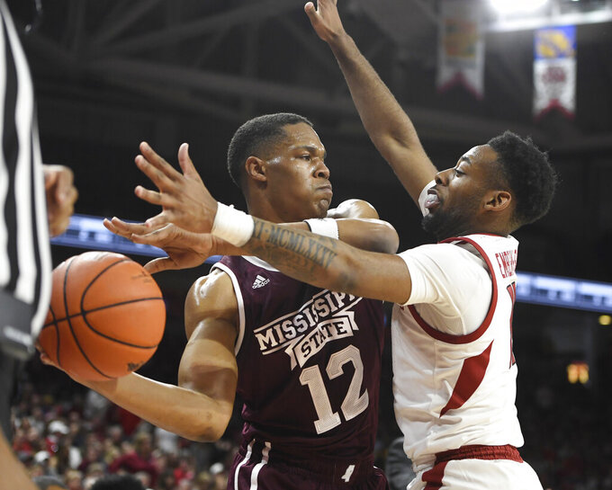 Arkansas defender Keyshawn Embery-Simpson puts pressure on Mississippi State guard Robert Woodard II during the first half of an NCAA college basketball game Saturday, Feb. 16, 2019, in Fayetteville, Ark. (AP Photo/Michael Woods)