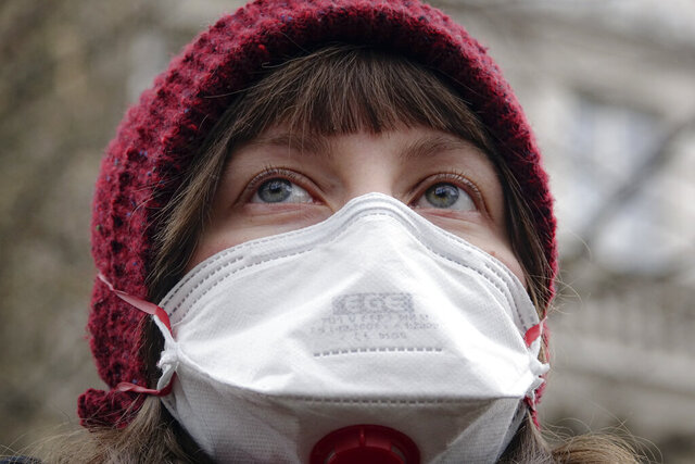 A woman wearing a gas mask takes part in a protest against air pollution, in Sarajevo, Bosnia, Monday, Jan. 20, 2020. Dozens of people, some wearing face masks, gathered for a protest because of dangerously high levels of air pollution in the past weeks in the Bosnian capital after measurements in the past weeks have shown that levels of damaging airborne particles have exceeded European Union's safety norms by several times.(AP Photo/Eldar Emric)
