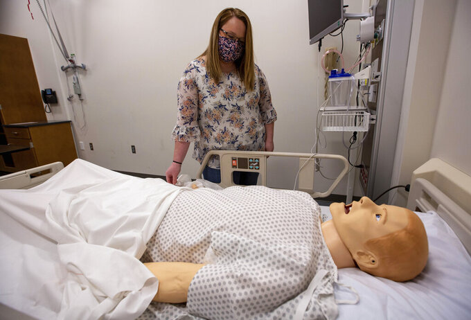 In this May 11, 2021 photo, Heather Fitzgerald, a recent Blue Ridge Community College nursing graduate, attaches a pulse oximeter to a mannequin in a nursing lab in Weyers Cave, Va. (Daniel Lin/Daily News-Record via AP)