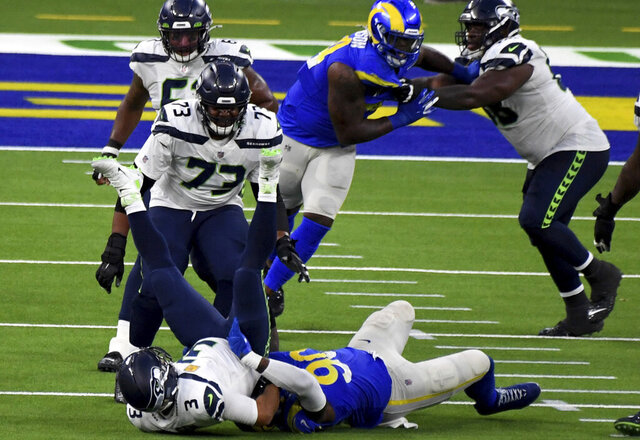 Los ANgeles Rams defensive end Michael Brockers (90) sacks Seattle Seahawks quarterback Russell Wilson (3) in the fourth quarter of an NFL football game in Inglewood, Calif., Sunday, Nov. 15, 2020. (Keith Birmingham/The Orange County Register via AP)