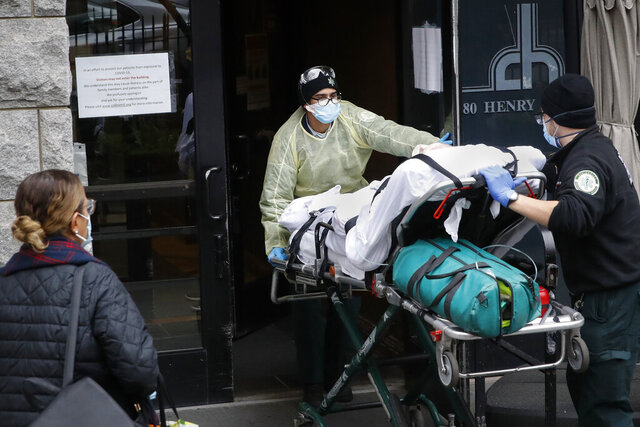 FILE- In this April 17, 2020, file photo, a patient is wheeled into Cobble Hill Health Center by emergency medical workers in the Brooklyn borough of New York. On Thursday, April 23, 2020, New York Gov. Andrew Cuomo said that nursing homes in New York must immediately report how they have complied with regulations for resident care during the coronavirus, and non-compliant facilities could face hefty fines or lose their licenses. (AP Photo/John Minchillo, File)