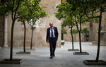 Catalan regional president Quim Torra walks at the Palace of the Generalitat, the headquarters of the Government of Catalonia, ahead of an interview with The Associated Press in Barcelona, Spain, Monday, Oct. 21, 2019. The leader of Catalonia says that the massive protests that have often spiralled into violent clashes with police this week won't cease until the Spanish government accepts to listen to separatists' demands. (AP Photo/Emilio Morenatti)