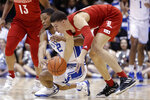 Duke guard Cassius Stanley (2) and Louisville guard Samuell Williamson, right, reach for a loose ball during the first half of an NCAA college basketball game in Durham, N.C., Saturday, Jan. 18, 2020. (AP Photo/Gerry Broome)
