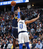 Denver Nuggets forward Paul Millsap shoots over Dallas Mavericks guard Jalen Brunson during the first half of an NBA basketball game Thursday, March 14, 2019, in Denver. (AP Photo/David Zalubowski)