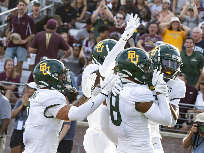 Baylor's JT Woods, right, celebrates with safety Jalen Pitre, center right, and other teammates after his interception for a touchdown during the first half of the team's NCAA college football game Texas State, Saturday, Sept. 4, 2021, in San Marcos, Texas. Baylor won 29-20. (AP Photo/Michael Thomas)