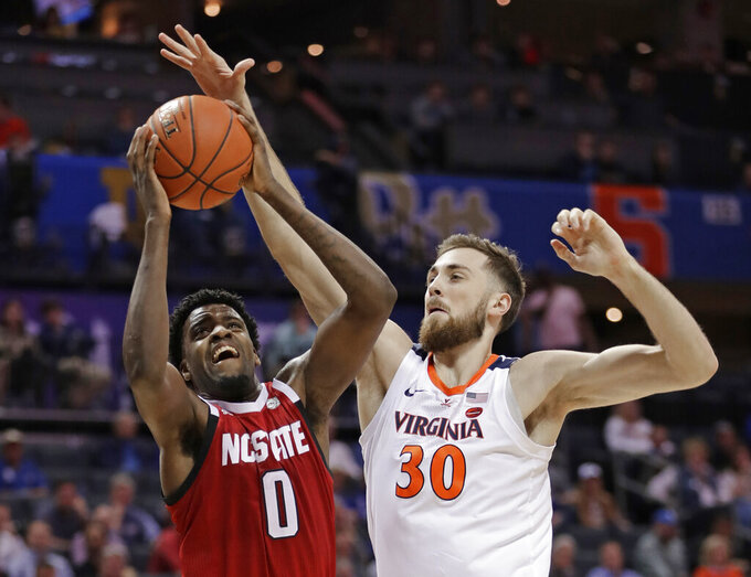 North Carolina State's DJ Funderburk (0) shoots against Virginia's Jay Huff (30) during the first half of an NCAA college basketball game in the Atlantic Coast Conference tournament in Charlotte, N.C., Thursday, March 14, 2019. (AP Photo/Nell Redmond)