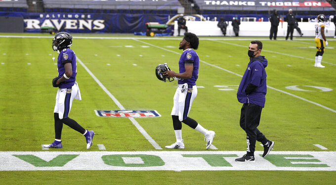 The word vote is seen on the sideline as Baltimore Ravens quarterbacks, from left, Lamar Jackson, Robert Griffin III and Trace McSorley walk on the field prior to an NFL football game against the Pittsburgh Steelers, Sunday, Nov. 1, 2020, in Baltimore. (AP Photo/Nick Wass)