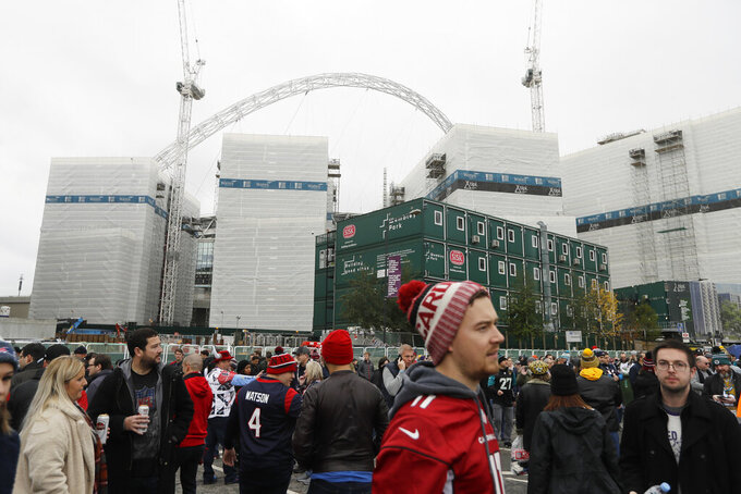 Fans walk outside the stadium before the first half of an NFL football game between the Houston Texans and the Jacksonville Jaguars at Wembley Stadium, Sunday, Nov. 3, 2019, in London. (AP Photo/Kirsty Wigglesworth)
