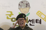 South Korean army Sergeant Byun Hui-su salutes during a press conference at the Center for Military Human Right Korea in Seoul, South Korea, Wednesday, Jan. 22, 2020. South Korea's military decided Wednesday to discharge Byun who recently undertook gender reassignment surgery, a ruling expected to draw strong criticism from human rights groups.The sign reads