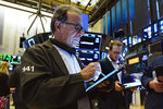 Traders Sal Suarino, left, and Ben Tuchman work on the floor of the New York Stock Exchange, Friday, July 16, 2021. Stocks are off to a slightly higher start on Wall Street Friday with an assist from several big technology companies. (AP Photo/Richard Drew)