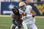 Long Island wide receiver Steven Chambers, right, is defended by West Virginia cornerback Charles Woods (9) during the first half of an NCAA college football game in Morgantown, W.Va., Saturday, Sept., 11, 2021. (AP Photo/Kathleen Batten)