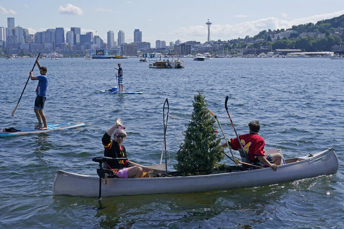 People paddle a canoe with a Christmas tree held up by hockey sticks as they float on Lake Union with the Space Needle in the background, Wednesday, July 21, 2021, in Seattle near the park where the Seattle Kraken NHL hockey expansion draft event was taking place. (AP Photo/Ted S. Warren)