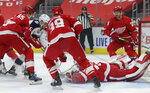 Detroit Red Wings goaltender Jonathan Bernier, right, lays out to stop a shot by Columbus Blue Jackets center Max Domi (16) as Red Wings defenseman Danny DeKeyser (65) and right-wing Anthony Mantha (39) help defend during the first period of an NHL hockey game Tuesday, Jan. 19, 2021, in Detroit. (AP Photo/Duane Burleson)